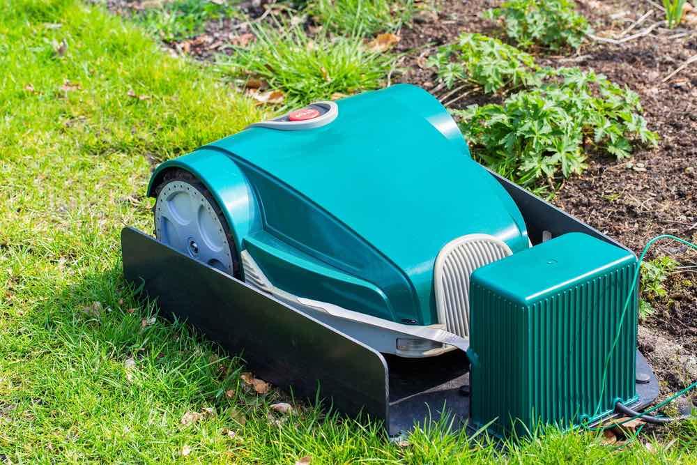 Robot grasmaaier aan het opladen bij het bassisstation