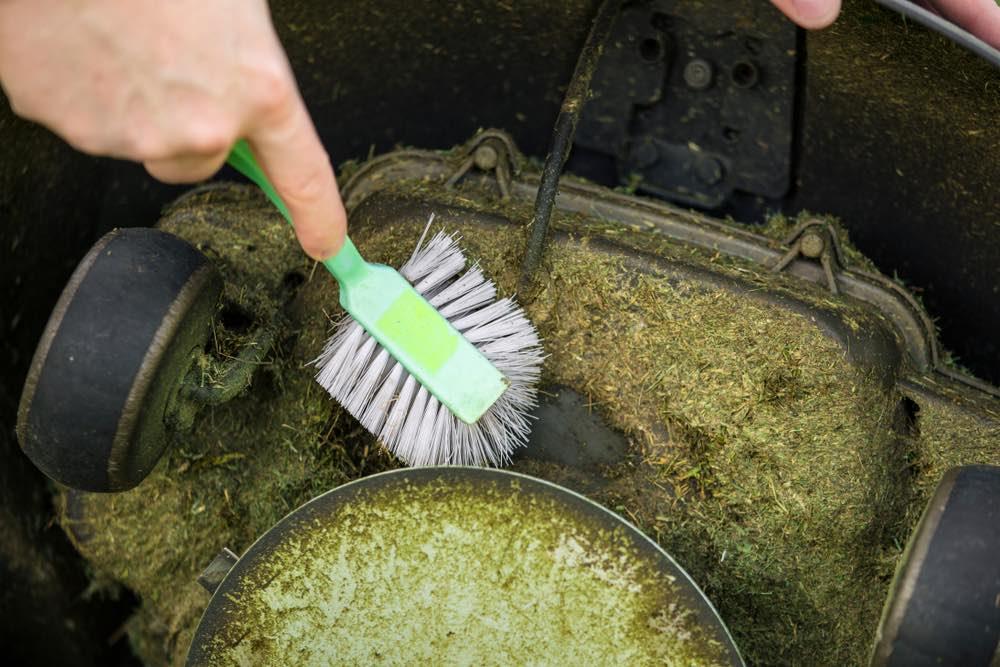Met een borstel de robot grasmaaier schoonmaken
